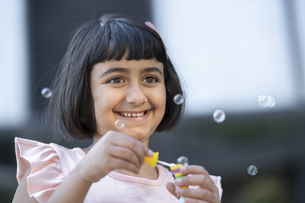 A girl wearing a pink shirt and pink bow blows bubbles in the Healing Garden at Children's National Hospital.