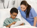 nurse with boy in hospital bed
