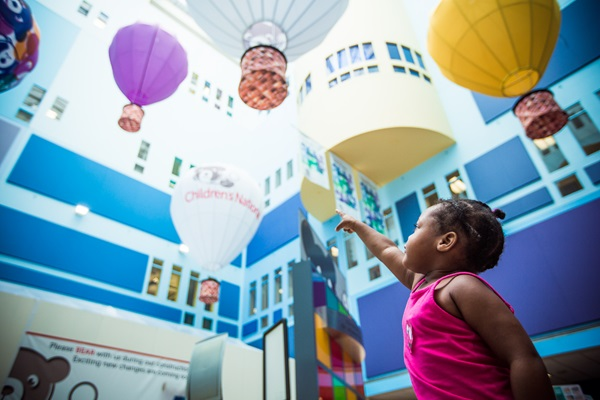 little girl pointing at atrium balloons