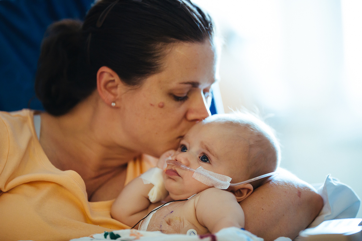 A mom kisses her infant, Children's National Health System Pediatric Cardiac Intensive Care Unit in Washington D C.