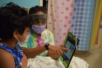 Child life specialist with young girl looking at tablet
