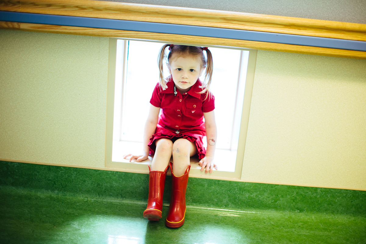 girl sitting with red dress and rainboots