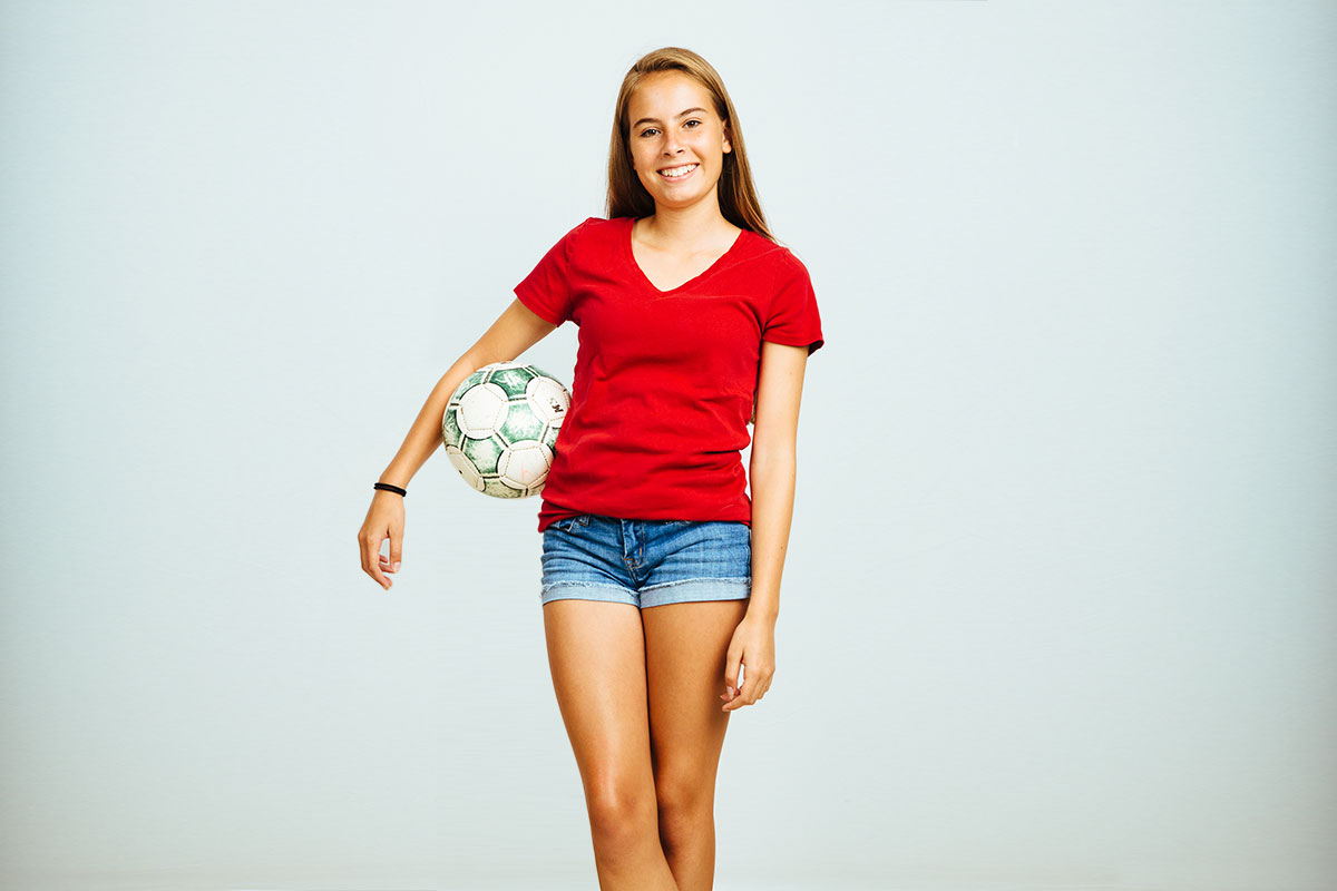 teen girl holding soccer ball