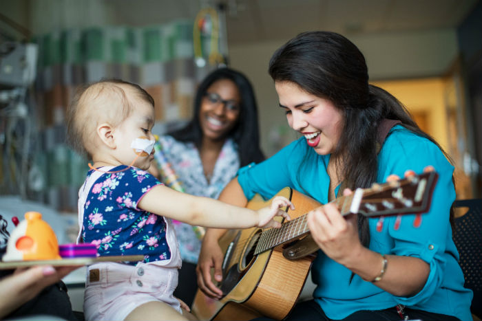 Music therapist appears with young patient.