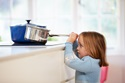 Little girl pulling pot off of stove