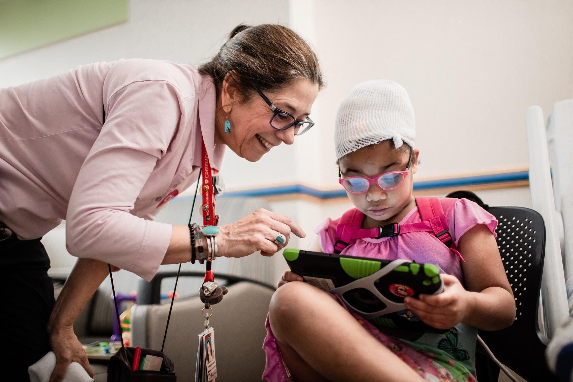 A girl with autism looks at a tablet device while a Children's National caregiver assists her.