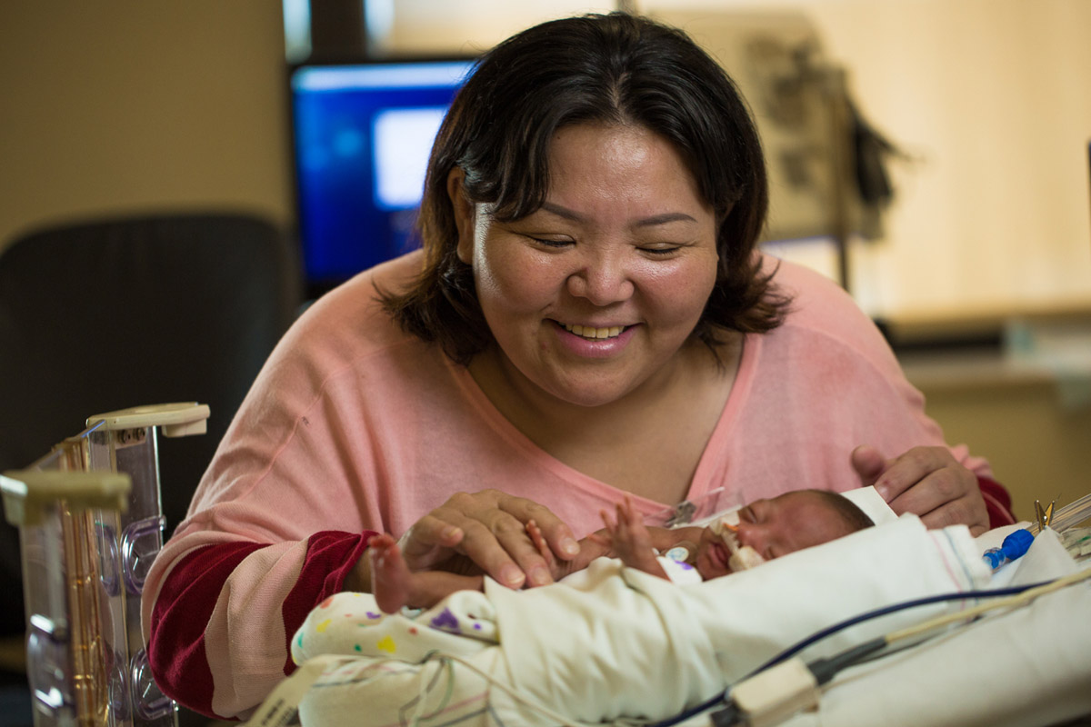 mother caring for premature baby in children's hospital NICU