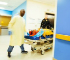 Patient being wheeled through hallway on hospital bed