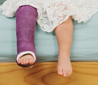 Little girl sitting on bed with cast on her leg