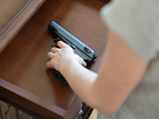 child reaching into drawer for gun