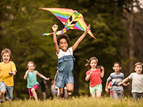 happy children running with a kite