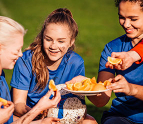 Girls soccer team eating orange slices