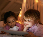 Two little girls at a sleep over using a tablet