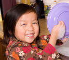 Little girl helping wash dishes