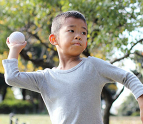 Young boy throwing a ball at the park