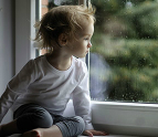 Sad toddler looking out a window at the rain