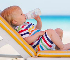 Baby drinking a bottle on the beach