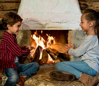 Boy and girl sitting by the fireplace