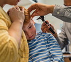 Boy getting his ear examined by doctor