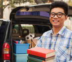 Teenage boy unpacking car at college