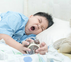 Boy yawning holding an alarm clock in bed
