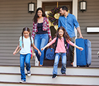 Family with luggage leaving house