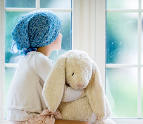 Girl holding a stuffed rabbit looking out the window
