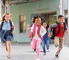 Kids running in school hallway with backpacks