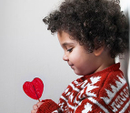 Boy holding a heart shaped lollipop