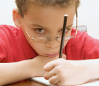 Boy wearing glasses holding a pencil