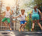 Three kids jumping on a trampoline