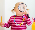 Toddler girl looking through a magnifying glass