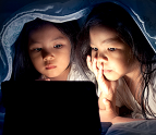 Two girls in bed looking at a tablet