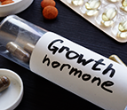 Bottle labeled Growth Hormone with pills