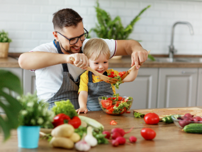father with son preparing a salad
