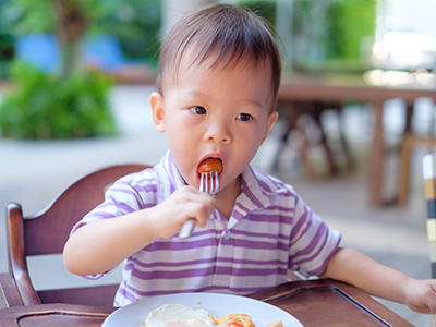 little boy eating tomatoes