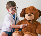 Little boy listenting to stuffed bear's heartbeat