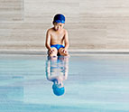 little boy sitting by swimming pool