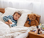 sick boy sleeping in bed with teddy bear