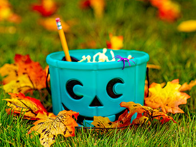 teal bucket containing non-food Halloween treats