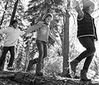 three kids walking on a log in the woods
