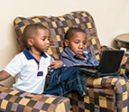 two boys sitting on a couch looking at a laptop