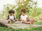 two kids reading books outside