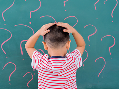 boy in front of board with question marks