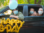 family celebrating birthday by social distancing in car