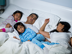 family sleeping in bed together