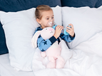 little girl in bed using asthma inhaler