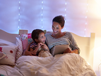 mom reading to kid in bed