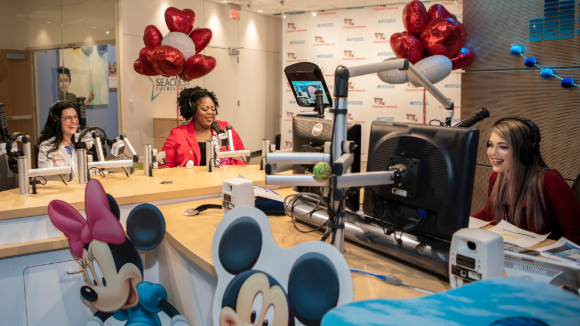 Surrounded by heart balloons, Children's National female radio hosts announce the name of the new cardiac intensive care unit robot: Dr. Bear Bot.