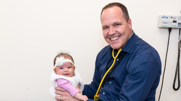 Timothy Kane, M.D., holds an infant girl wearing a headband.